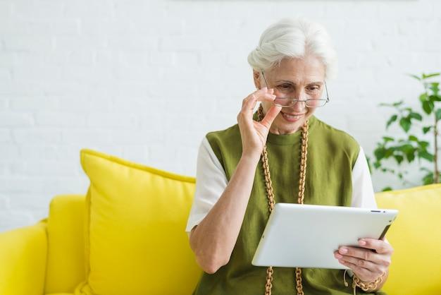 Portrait de femme senior heureuse en regardant tablette numérique Photo gratuit