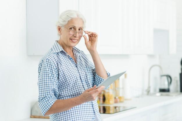Portrait de femme senior souriante tenant la tablette numérique debout dans la cuisine Photo gratuit