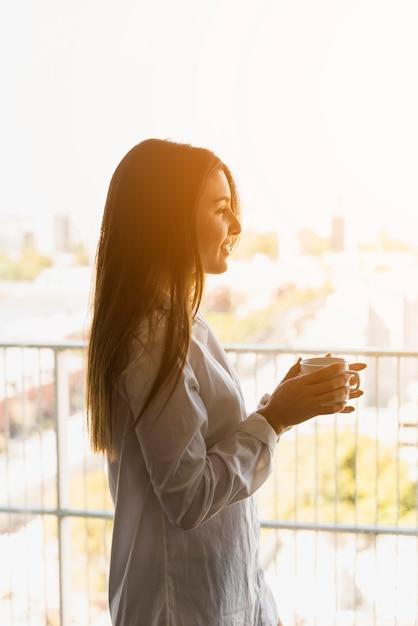 Portrait, de, a, femme souriante, apprécier, les, matin, café, sur, les, balcon Photo gratuit