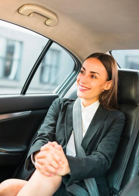 Portrait d'une femme souriante assise à l'intérieur d'une voiture Photo gratuit