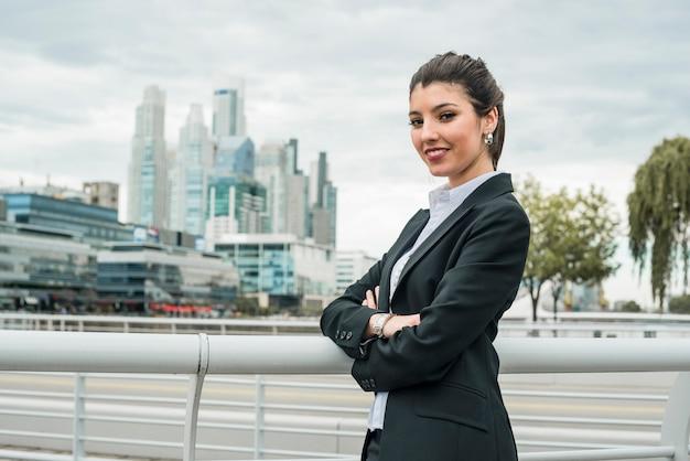 Portrait d'une femme souriante, debout devant le paysage urbain Photo gratuit