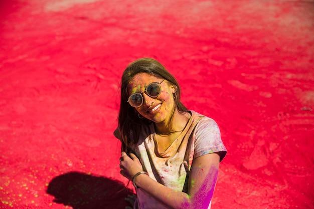 Portrait d'une femme souriante debout sur la poudre de couleur rouge holi Photo gratuit