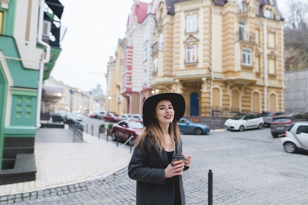Portrait D'une Femme Souriante élégante Se Promener Dans Une Belle Vieille Ville Avec Une Tasse De Boisson Chaude Dans Ses Mains. Photo Premium