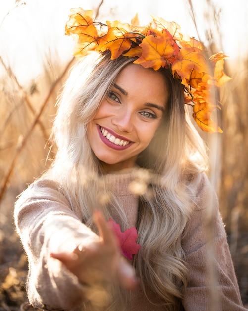 Portrait, de, femme souriante, porter, érable, feuilles, couronne, dehors Photo gratuit