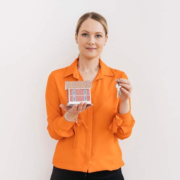 Portrait de femme tenant une paire de clés et une maison modèle isolée sur fond blanc Photo gratuit