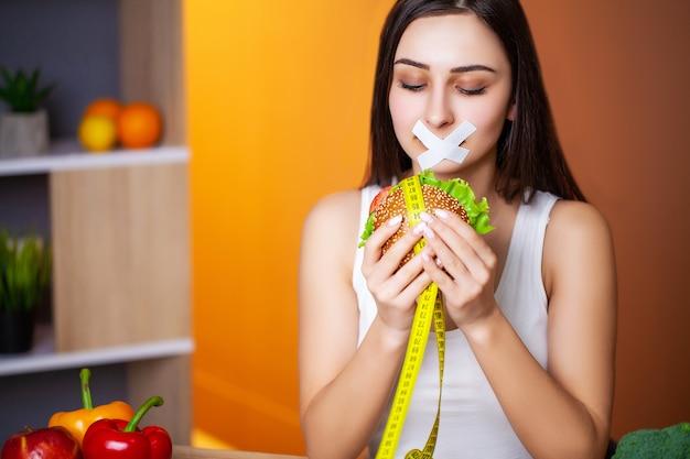 Portrait Femme Veut Manger Un Hamburger Mais Coincé La Bouche Skochem, Le Concept De Régime. Photo Premium