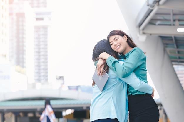 Portrait de femmes asiatiques heureux étreindre chaque fond de ville en plein air de l'ami Photo Premium