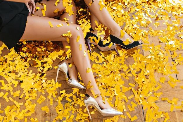 Portrait De Femmes Portant D'élégantes Chaussures à Talons Hauts Et Assis Sur Le Sol Pendant La Fête Photo gratuit