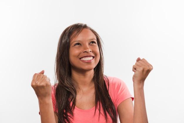 Portrait d'une fille africaine souriante célébrant la victoire Photo gratuit