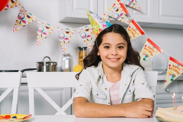 Portrait d'une fille d'anniversaire souriante portant chapeau de fête sur la tête en regardant la caméra Photo gratuit