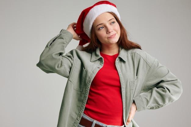Portrait D'une Fille Bonnets Rouges Avec Un Pompon Sur Fond Gris Vue Recadrée De Noël Nouvel An. Photo De Haute Qualité Photo Premium