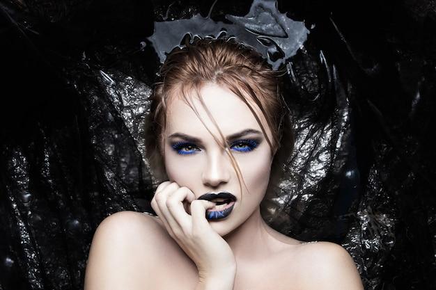 Portrait d'une fille dans l'eau avec une couleur bleue créative des cils et des lèvres Photo Premium
