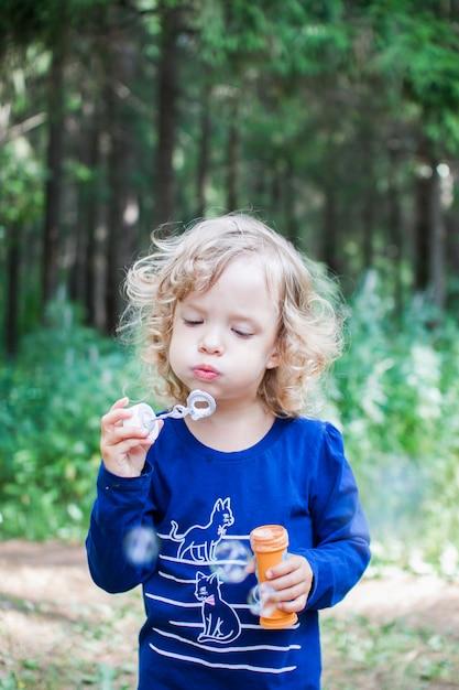 Portrait d'une fille frisée qui gonfle des bulles de savon Photo Premium
