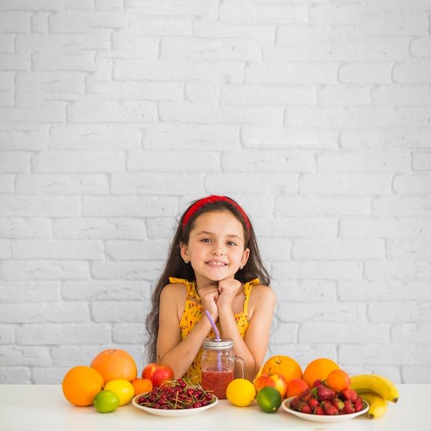 Portrait de fille avec des fruits sur le bureau blanc Photo gratuit