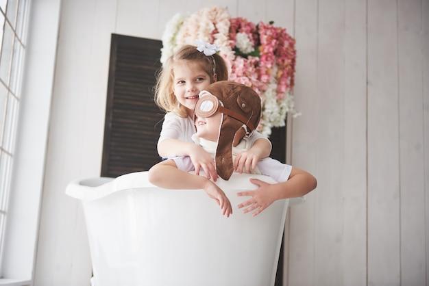 Portrait d'une fille et un garçon au chapeau de pilote jouant dans la salle de bain chez les pilotes ou les marins. voyage, enfance et réalisation de rêves Photo Premium