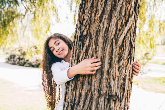 Portrait d'une fille heureuse embrassant un grand coffre dans le jardin Photo gratuit