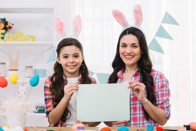 Portrait de fille et mère montrant un papier vierge le jour de pâques Photo gratuit