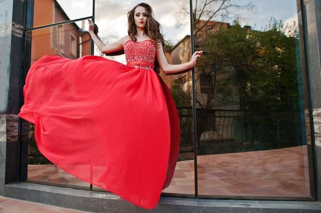 Portrait d'une fille à la mode à la robe de soirée rouge posée fenêtre miroir de fond du bâtiment moderne. robe soufflant dans l'air Photo Premium