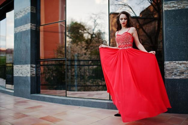Portrait d'une fille à la mode à la robe de soirée rouge posée fenêtre miroir de fond du bâtiment moderne Photo Premium