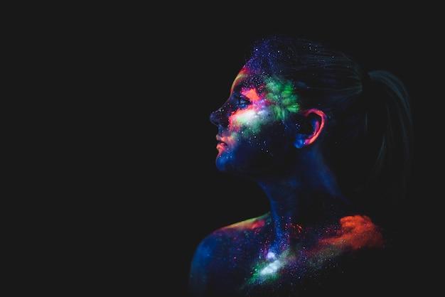 Portrait d'une fille peinte en couleurs uv fluorescentes. Photo Premium