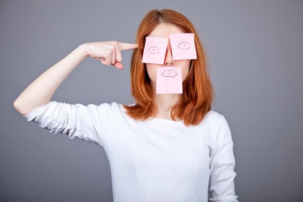 Portrait de fille rousse avec des autocollants colorés sur la bouche et les yeux. Photo Premium