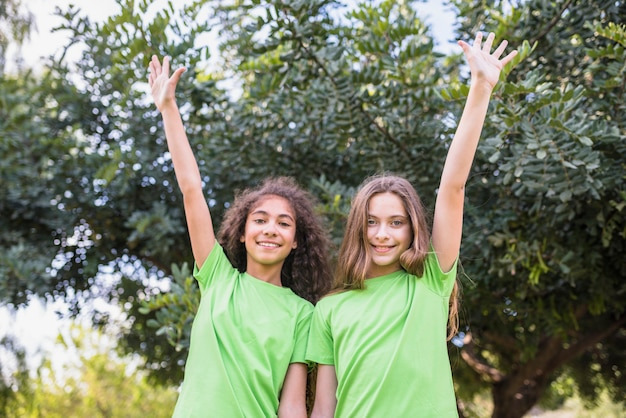 Portrait, de, a, fille souriante, lever bras, debout, devant, arbres Photo gratuit