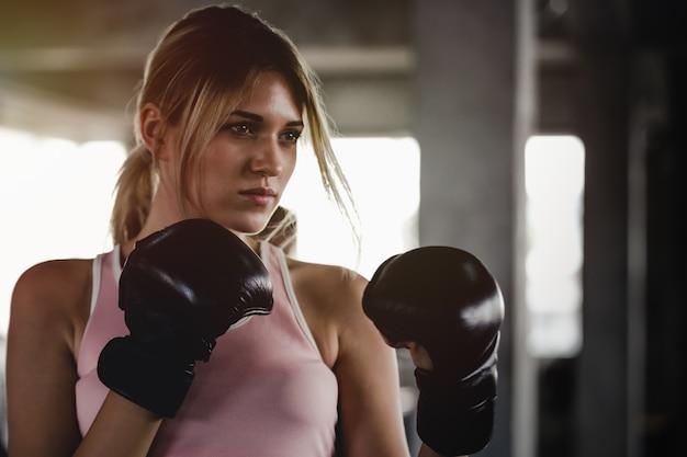 Portrait fille sportive belle femme avec les gants de boxe en arrière au gymnase Photo Premium