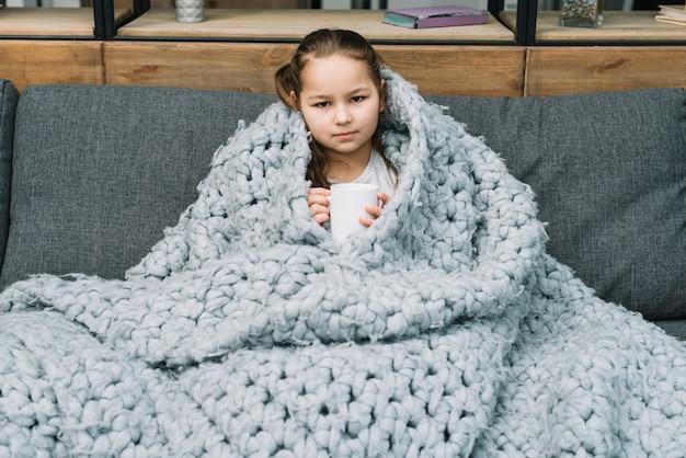 Portrait, fille, tasse, café, séance, sofa, couvert, écharpe Photo gratuit