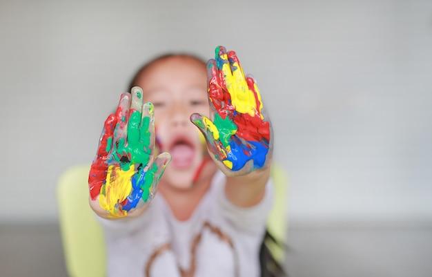 Portrait d'une fillette souriante regardant à travers ses mains colorées et sa joue peinte dans la chambre d'enfant. Photo Premium