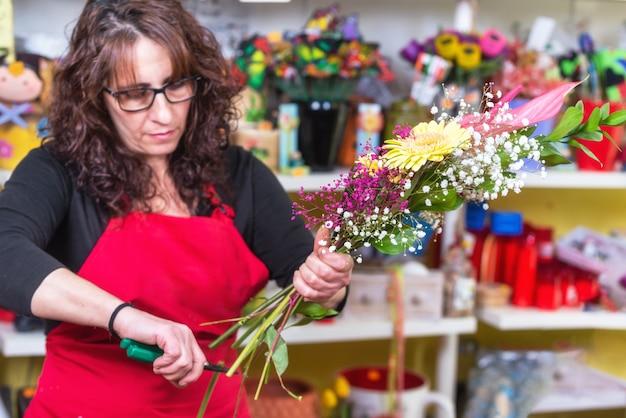 Portrait, de, fleuriste femme, porter, tablier, debout, à, compteur, faire, bouquet, à, client, à, fleuriste Photo Premium