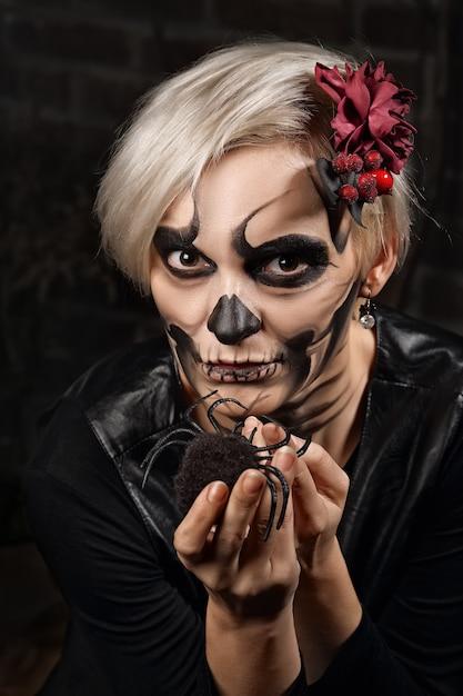 Portrait de flou artistique de visage de femme avec du maquillage de crâne de sucre tenant l'araignée dans les mains. art de la peinture faciale. Photo Premium