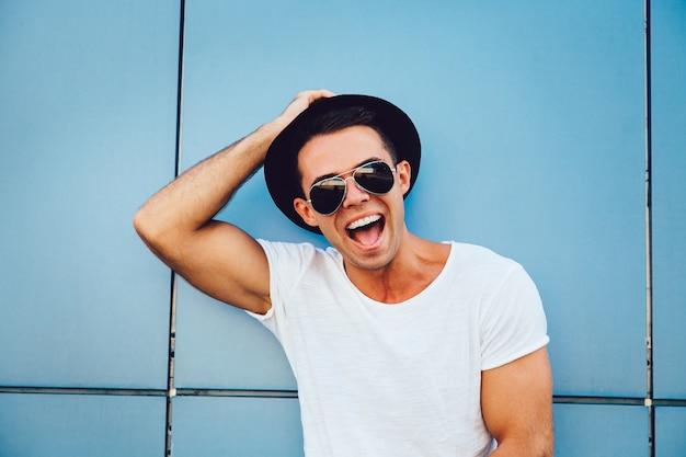 Portrait, de, a, gai, muscle, mec, dans, lunettes soleil, et, chapeau, regarder appareil-photo, et, sourire, largement Photo gratuit