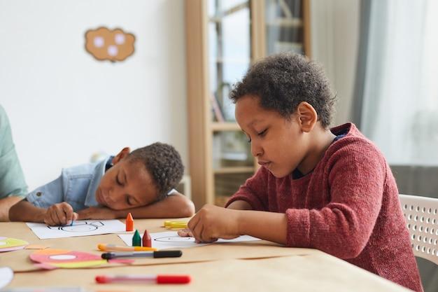Portrait De Garçon Afro-américain Dessinant Des Images Avec Des Crayons Tout En Profitant De Cours D'art à L'école Maternelle Photo Premium
