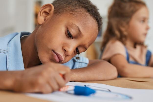Portrait De Garçon Afro-américain, Dessinant Des Images Avec Des Crayons Tout En Profitant De Cours D'art En Maternelle Ou Centre De Développement Photo Premium