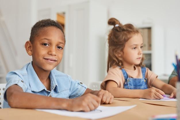 Portrait De Garçon Afro-américain Souriant Tout En Dessinant Des Images Avec Des Crayons Pendant Les Cours D'art à L'école Maternelle Photo Premium