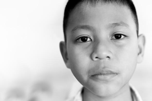 Portrait d'un garçon asiatique qui pleure avec une larme sur son visage en noir et blanc. Photo Premium