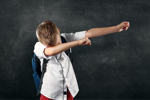 Portrait d'un garçon d'une école primaire sur fond d'une commission scolaire Photo Premium