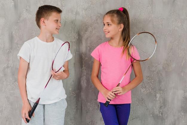 Portrait, garçon, fille, tenue, raquette, main, debout, devant, mur béton Photo gratuit