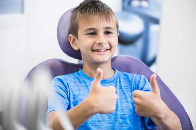 Portrait d'un garçon heureux gesticulant pouce en l'air à la clinique Photo gratuit
