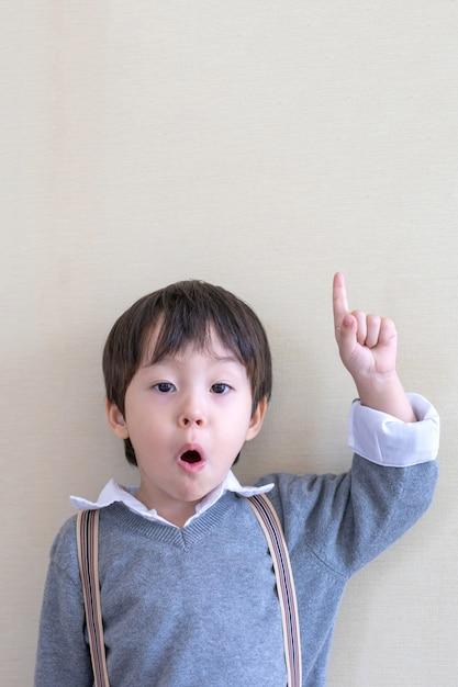 Portrait garçon mignon, pointant vers le haut sur blanc Photo gratuit