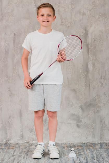 Portrait, garçon, raquette, volant, debout, devant, béton, mur Photo gratuit