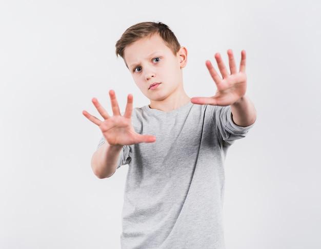 Portrait D'un Garçon à La Recherche D'appareil Photo Faisant Un Geste D'arrêt Isolé Sur Fond Blanc Photo gratuit