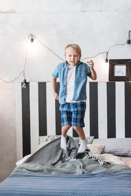 Portrait, garçon, sauter, lit, décoré, éclairé, lumière, mur Photo gratuit