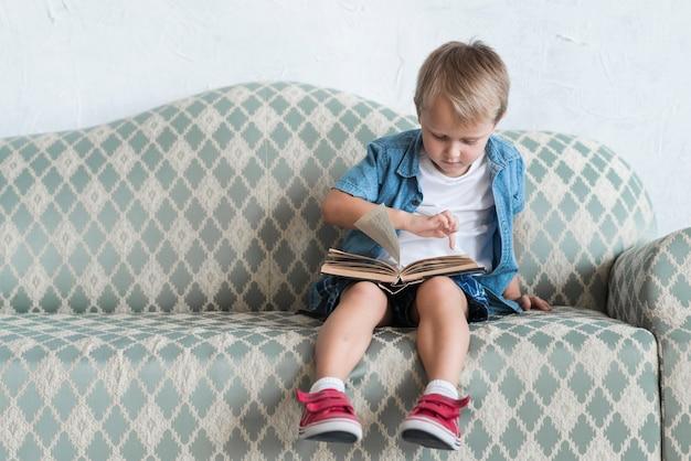 Portrait, garçon, séance, sofa, pointage doigt, livre Photo gratuit