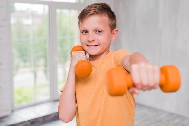 Portrait d'un garçon souriant, entraînement avec haltère Photo gratuit