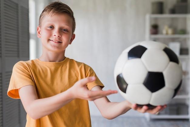 Portrait d'un garçon souriant montrant un ballon de foot Photo gratuit