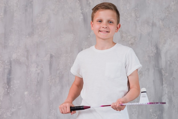 Portrait, de, a, garçon souriant, tenue, raquette, et, volant, regarder appareil-photo Photo gratuit