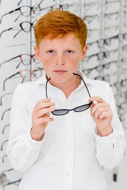 Portrait de garçon de taches de rousseur en regardant la caméra tout en tenant des lunettes Photo gratuit