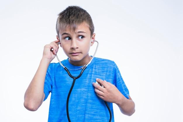 Portrait d'un garçon vérifiant son rythme cardiaque avec stéthoscope sur fond blanc Photo gratuit