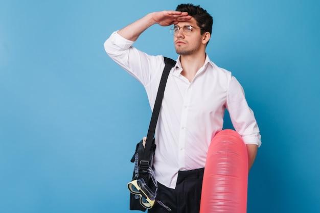 Portrait De Gars à La Recherche De Distance Sur L'espace Bleu. Homme En Chemise Blanche Et Lunettes Tenant Un Cercle Gonflable. Photo gratuit
